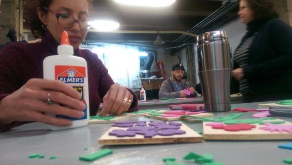 Artist and workshop instructor Sophie Sanders glues felt cutouts onto blocks to make stamps.