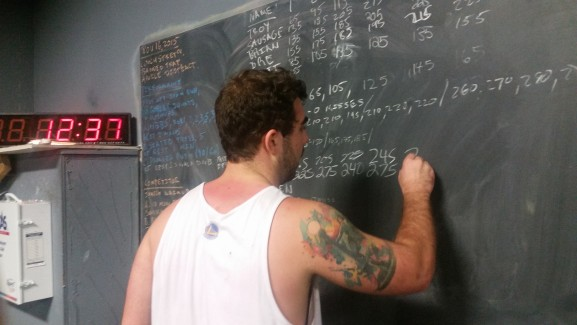 A gym member writes down the weight of his completed reps.