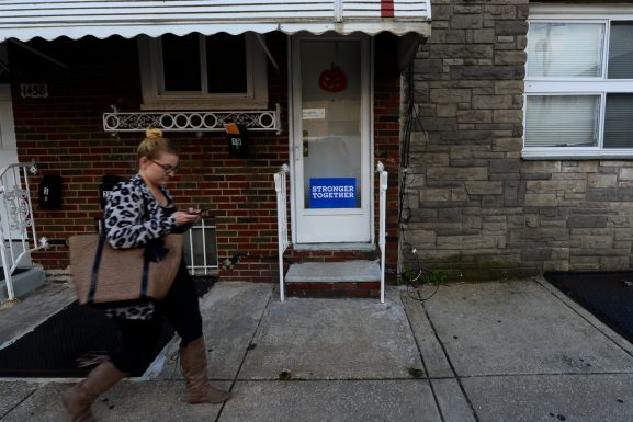A woman walks by a sign supporting Democratic candidate Hillary Clinton for president in Point Breeze, Philadelphia. The Clinton campaign has put out an extensive HIV/AIDS platform, with no alternative from Republican candidate Donald Trump.