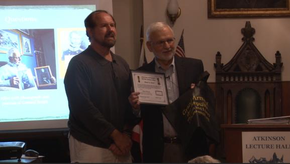 Allen Mesch receiving a certificate of merti at the conclusion of his speech.