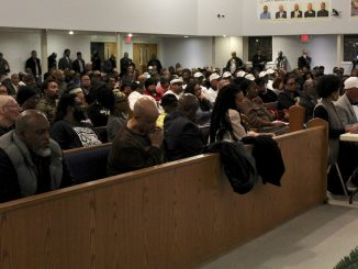 Several hundred people sit in the pews in a church. Two people are seated at a table in the front of the church, and one of them is speaking into a microphone.