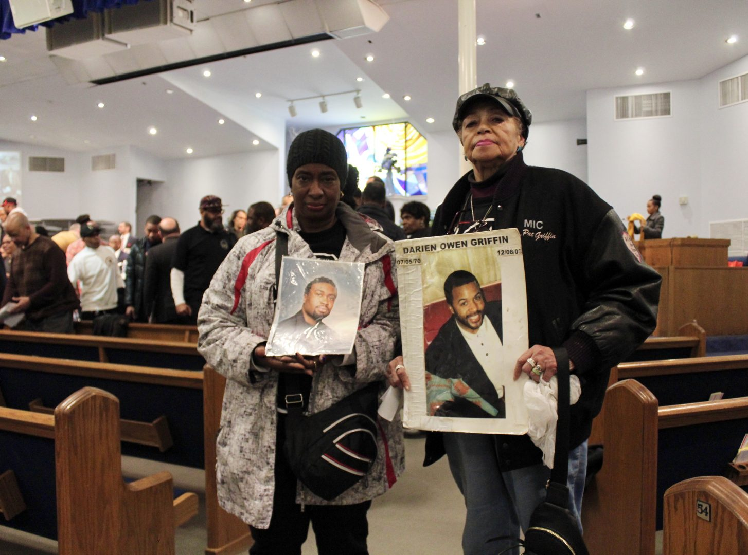 Valerie Jackson and Dr. Patricia Griffin stand between the pews in the church, facing the camera. They are holding posters with the photos of their sons, who were murdered. The poster of Griffin's son also includes his name, Darien Owen Griffin, and the dates of his birth and death.