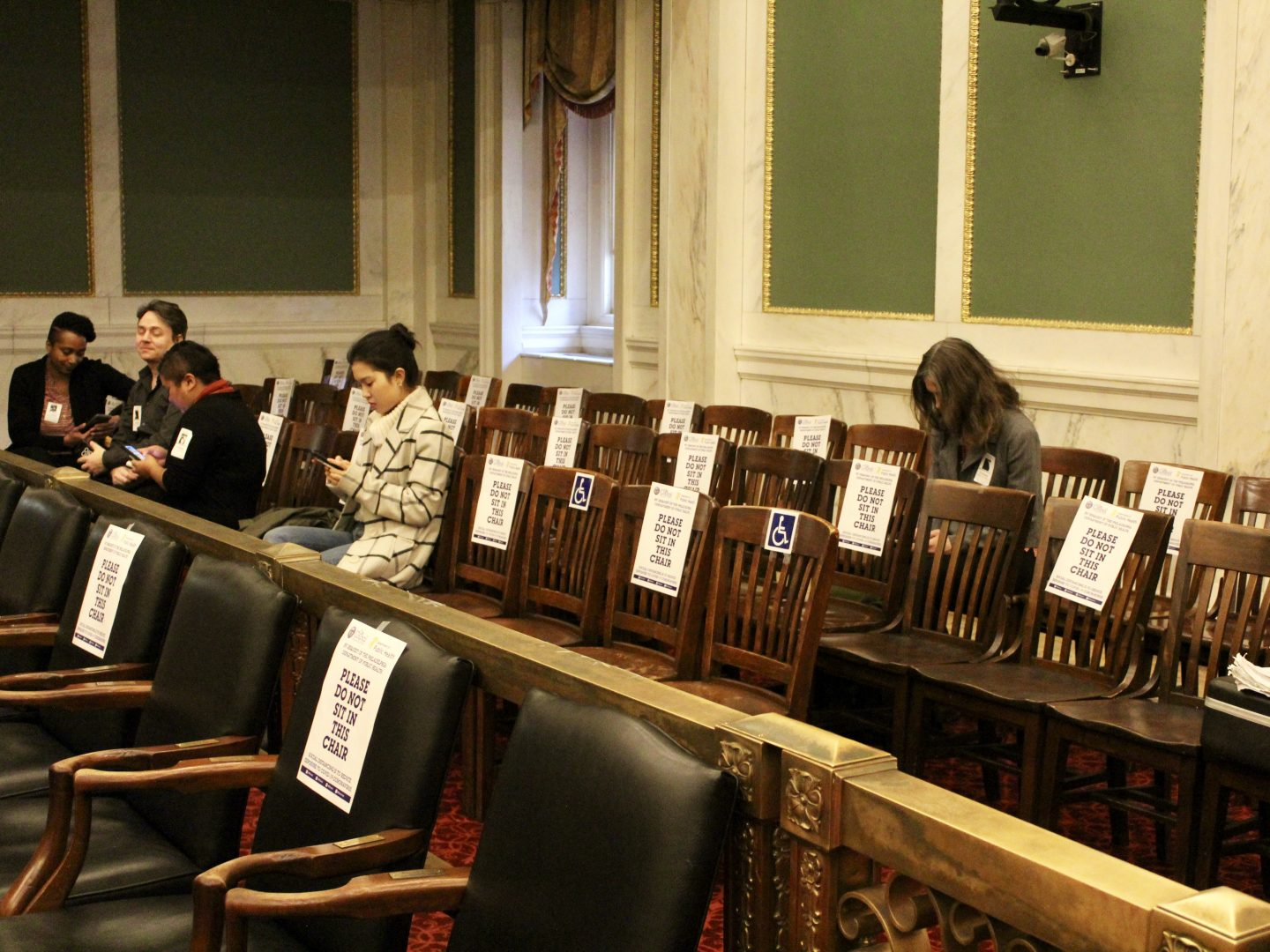 Five people sit in the audience section of city council. Every other chair is blocked.
